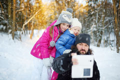 Dos pequeñas hermanas lindas que toman un selfie con su padre foto de archivo