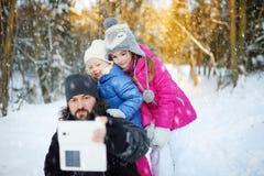 Dos pequeñas hermanas lindas que toman un selfie con su padre imagenes de archivo