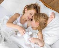 Dos pequeñas hermanas que abrazan en cama Foto de archivo libre de regalías