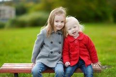 Dos pequeñas hermanas que abrazan en un banco Imagen de archivo libre de regalías