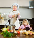 Dos pequeñas hermanas que aprenden cómo cocinar fotos de archivo