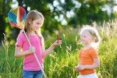 Dos pequeñas hermanas que cogen mariposas e insectos con sus cucharada-redes imágenes de archivo libres de regalías