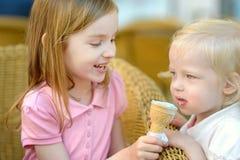 Dos pequeñas hermanas que comen el helado al aire libre Foto de archivo