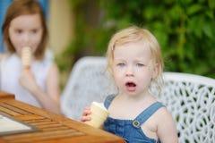 Dos pequeñas hermanas que comen el helado al aire libre Imagen de archivo