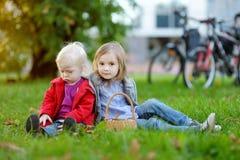 Dos pequeñas hermanas que juegan afuera Fotos de archivo libres de regalías