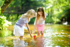 Dos pequeñas hermanas que juegan con los barcos de papel por un río en día de verano caliente y soleado Niños que se divierten po imagen de archivo