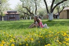 Dos pequeñas hermanas que juegan en el jardín imágenes de archivo libres de regalías