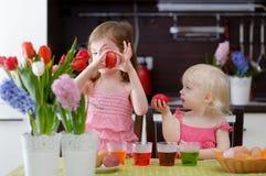Dos pequeñas hermanas que pintan los huevos de Pascua Fotografía de archivo