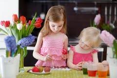 Dos pequeñas hermanas que pintan los huevos de Pascua Imágenes de archivo libres de regalías