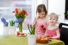 Dos pequeñas hermanas que pintan los huevos de Pascua Imagen de archivo libre de regalías