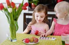 Dos pequeñas hermanas que pintan los huevos de Pascua Fotografía de archivo libre de regalías