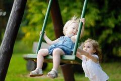 Dos pequeñas hermanas que se divierten en un oscilación Fotografía de archivo libre de regalías