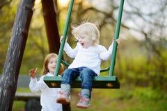 Dos pequeñas hermanas que se divierten en un oscilación Imagen de archivo libre de regalías