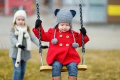 Dos pequeñas hermanas que se divierten en un oscilación Foto de archivo libre de regalías