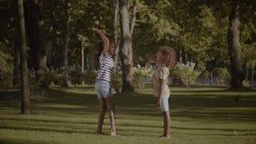 Dos pequeñas hermanas sonrientes que dan el alto cinco al aire libre almacen de video