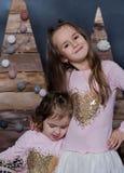 Dos pequeñas hermanas ven algo en su mano Imagen de archivo libre de regalías