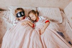Dos pequeñas hermanas vestidas en los pijamas que duermen en la cama en el dormitorio fotos de archivo