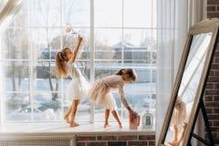 Dos pequeñas hermanas vestidas en los vestidos hermosos se colocan en el alféizar al lado del espejo el invierno afuera imagen de archivo