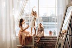 Dos pequeñas hermanas vestidas en los vestidos hermosos y allí madre joven para sentarse en el alféizar al lado del espejo foto de archivo