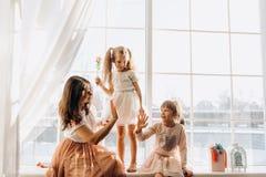 Dos pequeñas hermanas vestidas en los vestidos hermosos y allí madre joven para sentarse en el alféizar al lado del espejo foto de archivo libre de regalías