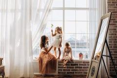 Dos pequeñas hermanas vestidas en los vestidos hermosos y allí madre joven para sentarse en el alféizar al lado del espejo fotos de archivo libres de regalías