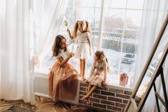 Dos pequeñas hermanas vestidas en los vestidos hermosos y allí madre joven para sentarse en el alféizar al lado del espejo fotos de archivo