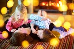 Dos pequeñas hermanas y su madre que disfrutan de su tiempo junto el mañana de la Navidad fotografía de archivo