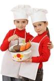 Dos pequeñas jefe-cocinas que sostienen un crisol Foto de archivo libre de regalías
