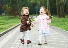 Dos pequeñas muchachas de risa de los cabritos al aire libre Imagen de archivo libre de regalías