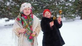 Dos pequeñas muchachas en ropa y pañuelos en el estilo ruso juegan en las cucharas de madera contra la perspectiva de nieve almacen de metraje de vídeo