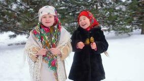 Dos pequeñas muchachas en ropa y pañuelos en el estilo ruso juegan en las cucharas de madera contra la perspectiva de nieve metrajes