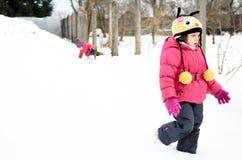 Dos pequeñas muchachas gemelas están jugando en la nieve Imágenes de archivo libres de regalías
