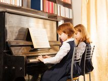 Dos pequeñas muchachas hermosas alegres que juegan el piano Fotos de archivo libres de regalías