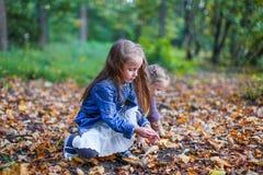 Dos pequeñas muchachas hermosas que se sientan en el amarillo Imagen de archivo libre de regalías