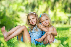 Dos pequeñas muchachas lindas en césped Fotos de archivo libres de regalías
