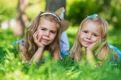 Dos pequeñas muchachas lindas en césped del verano Fotos de archivo libres de regalías