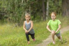 Dos pequeñas muchachas lindas que calientan al aire libre Fotografía de archivo