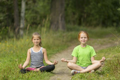 Dos pequeñas muchachas lindas que se sientan en la posición de Lotus en el parque Imagenes de archivo