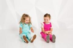 Dos pequeñas novias en los guardapolvos idénticos de diversos colores que se sientan en el piso en un estudio con las paredes bla Imagenes de archivo
