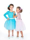 Dos pequeñas novias en los vestidos elegantes idénticos del diffe Imagen de archivo libre de regalías