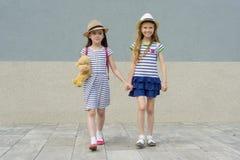 Dos pequeñas novias hermosas que llevan a cabo las manos, muchachas que caminan en los vestidos rayados, sombreros con la mochila fotografía de archivo