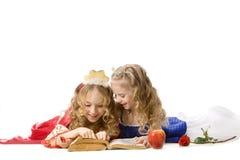 Dos pequeñas princesas felices Reading un libro mágico Fotos de archivo