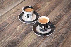 Dos pequeñas tazas de café en fondo de madera Imagen de archivo