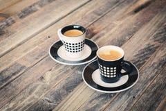 Dos pequeñas tazas de café en fondo de madera Imagen de archivo libre de regalías