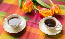 Dos pequeñas tazas de café en los platillos en la tabla con los tulipanes Imágenes de archivo libres de regalías