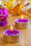 Dos pequeñas velas y bolas de la Navidad que brillan intensamente en el tablero de madera imágenes de archivo libres de regalías