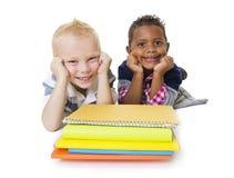 Dos pequeños alumnos diversos con sus libros Imagen de archivo