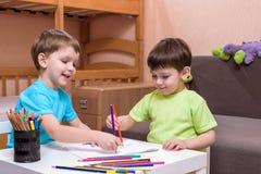 Dos pequeños amigos caucásicos que juegan con las porciones de bloques plásticos coloridos interiores Muchachos activos del niño, Fotos de archivo libres de regalías