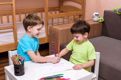 Dos pequeños amigos caucásicos que juegan con las porciones de bloques plásticos coloridos interiores Muchachos activos del niño, Fotos de archivo