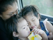 Dos pequeños bebés asiáticos, hermanos, abrazando en el revestimiento de su madre en un coche durante un viaje fotografía de archivo